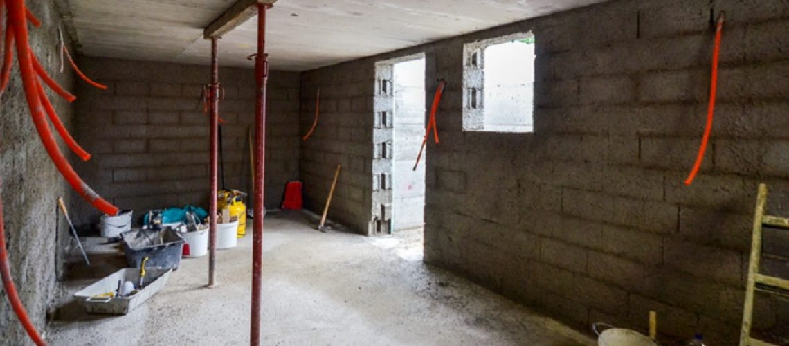 Plastering, rebuilding, waterproofing basement or a cellar and work tools. Construction of residential house cellar or basement with electric installations and freshly plastered walls.