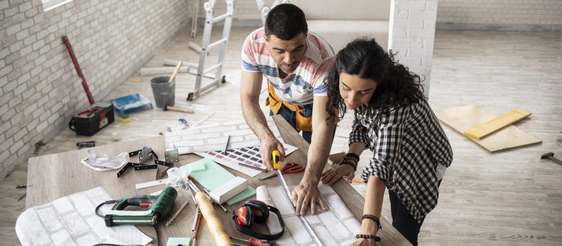 Couple making home improvement and measuring